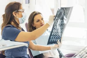 woman and dentist examine xray