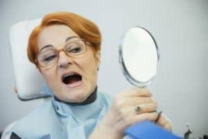 woman looking in mirror in dental chair