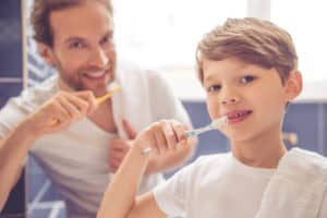 boy and dad brushing teeth
